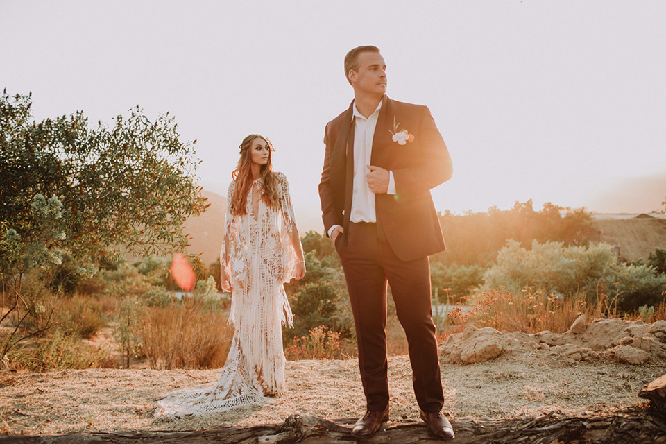 hey-babe-ranch-brode-and-groom-groom-in-foreground-looking-off-to-the-distance-hand-on-jacket-bride-in-a-bohemian-gown-with-lace-and-fringe-detailing-and-hair-in-a-loose-wave-groom-in-a-burgundy-tuxedo-with-black-satin-truim-and-his-tie-undone-for-a-relaxed-look