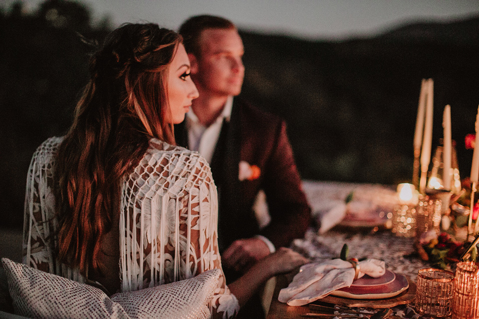 hey-babe-ranch-sunset-couple-picture-bride-in-a-bohemian-gown-with-lace-and-fringe-detailing-and-hair-in-a-loose-wave-groom-in-a-burgundy-tuxedo-with-black-satin-truim-and-his-tie-undone-for-a-relaxed-look