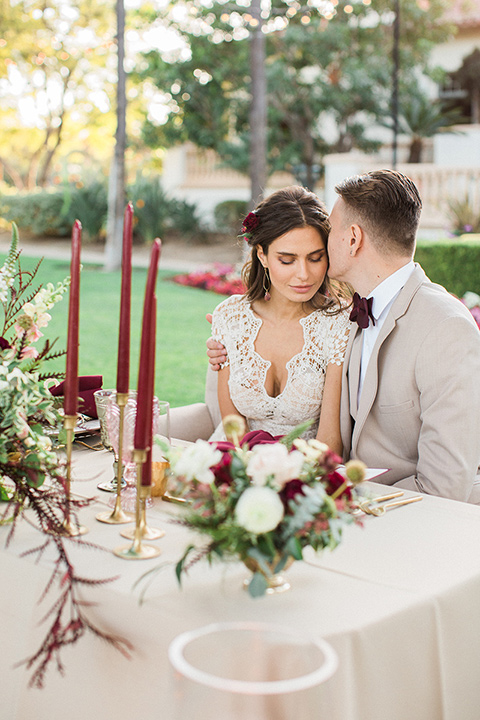 Huntington-bay-club-wedding-bride-and-groom-at-sweetheart-table-bride-in-a-spanish-inspired-style-dress-with-lace-detailing-and-cap-sleeves-groom-in-a-tan-suit-with-a-burgundy-matte-bow-tie-and-brown-shoes