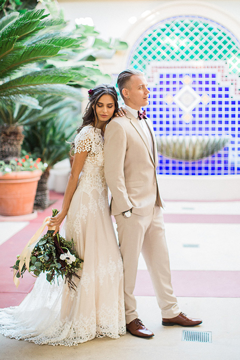 Huntington-bay-club-wedding-bride-and-groom-by-the-fountain-bride-in-a-spanish-inspired-style-dress-with-lace-detailing-and-cap-sleeves-groom-in-a-tan-suit-with-a-burgundy-matte-bow-tie-and-brown-shoes