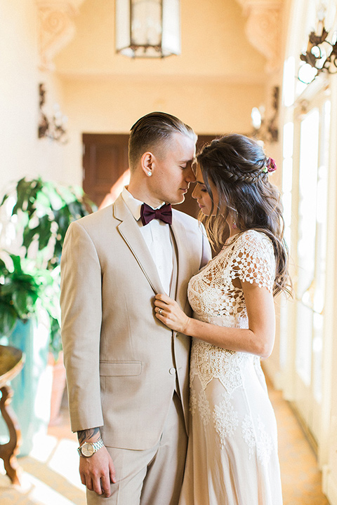 Huntington-bay-club-wedding-bride-and-groom-in-hallway-bride-in-a-spanish-inspired-style-dress-with-lace-detailing-and-cap-sleeves-groom-in-a-tan-suit-with-a-burgundy-matte-bow-tie-and-brown-shoes
