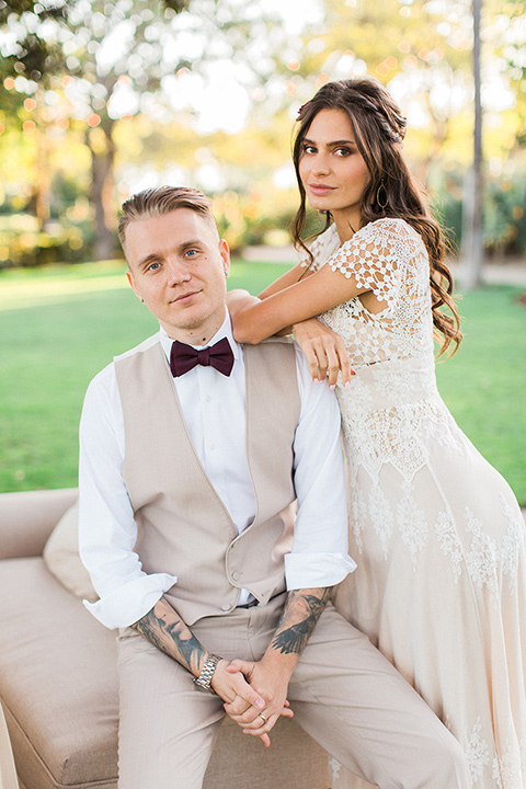 Huntington-bay-club-wedding-bride-and-groom-looking-at-camera-groom-with-no-jacket-bride-in-a-spanish-inspired-style-dress-with-lace-detailing-and-cap-sleeves-groom-in-a-tan-suit-with-a-burgundy-matte-bow-tie-and-brown-shoes