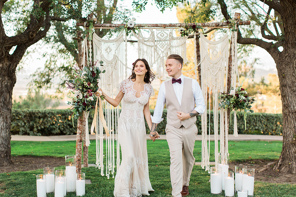 Huntington-bay-club-wedding-bride-and-groom-walking-down-the-aisle-bride-in-a-spanish-inspired-style-dress-with-lace-detailing-and-cap-sleeves-groom-in-a-tan-suit-with-a-burgundy-matte-bow-tie-and-brown-shoes