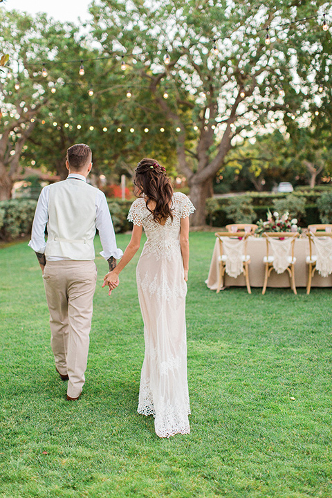 Huntington-bay-club-wedding-bride-and-groom-walking-towards-reception-bride-in-a-spanish-inspired-style-dress-with-lace-detailing-and-cap-sleeves-groom-in-a-tan-suit-with-a-burgundy-matte-bow-tie-and-brown-shoes