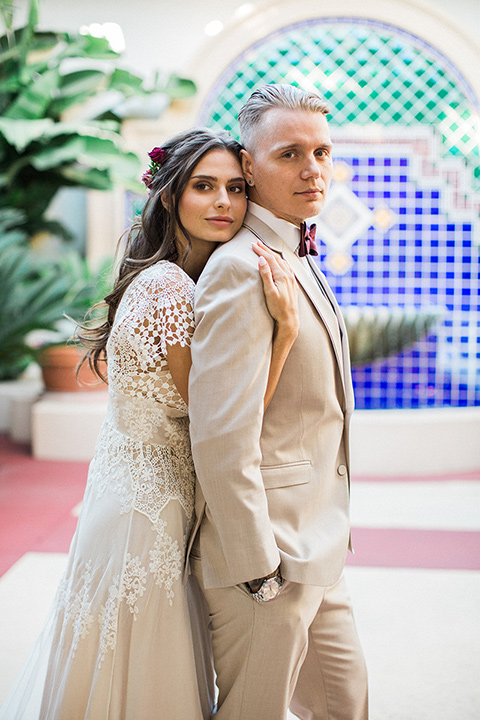 Huntington-bay-club-wedding-bride-behind-groom-bride-in-a-spanish-inspired-style-dress-with-lace-detailing-and-cap-sleeves-groom-in-a-tan-suit-with-a-burgundy-matte-bow-tie-and-brown-shoes