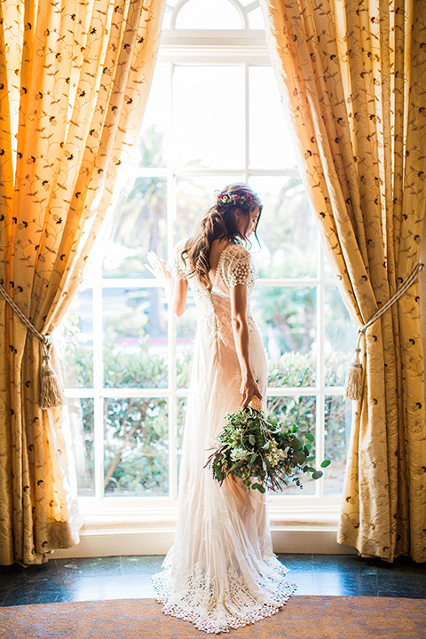 Huntington-bay-club-wedding-bride-by-window-bride-behind-groom-bride-in-a-spanish-inspired-style-dress-with-lace-detailing-and-cap-sleeves