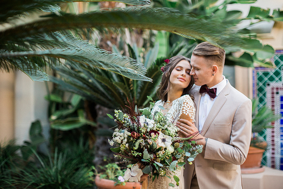 Huntington-bay-club-wedding-groom-behind-bride-bride-in-a-spanish-inspired-style-dress-with-lace-detailing-and-cap-sleeves-groom-in-a-tan-suit-with-a-burgundy-matte-bow-tie-and-brown-shoes