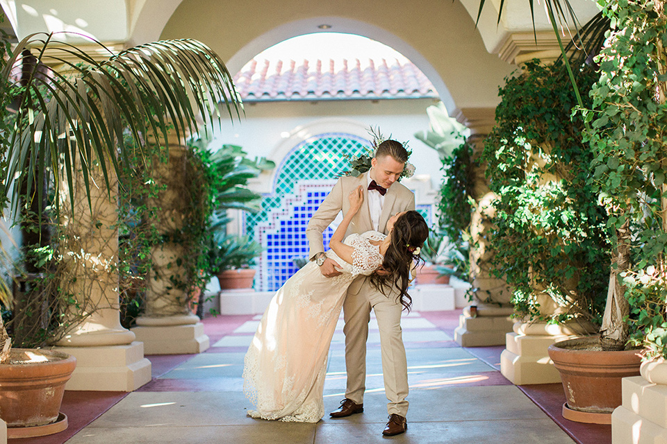 Huntington-bay-club-wedding-groom-dipping-bride-in-a-spanish-inspired-style-dress-with-lace-detailing-and-cap-sleeves-groom-in-a-tan-suit-with-a-burgundy-matte-bow-tie-and-brown-shoes