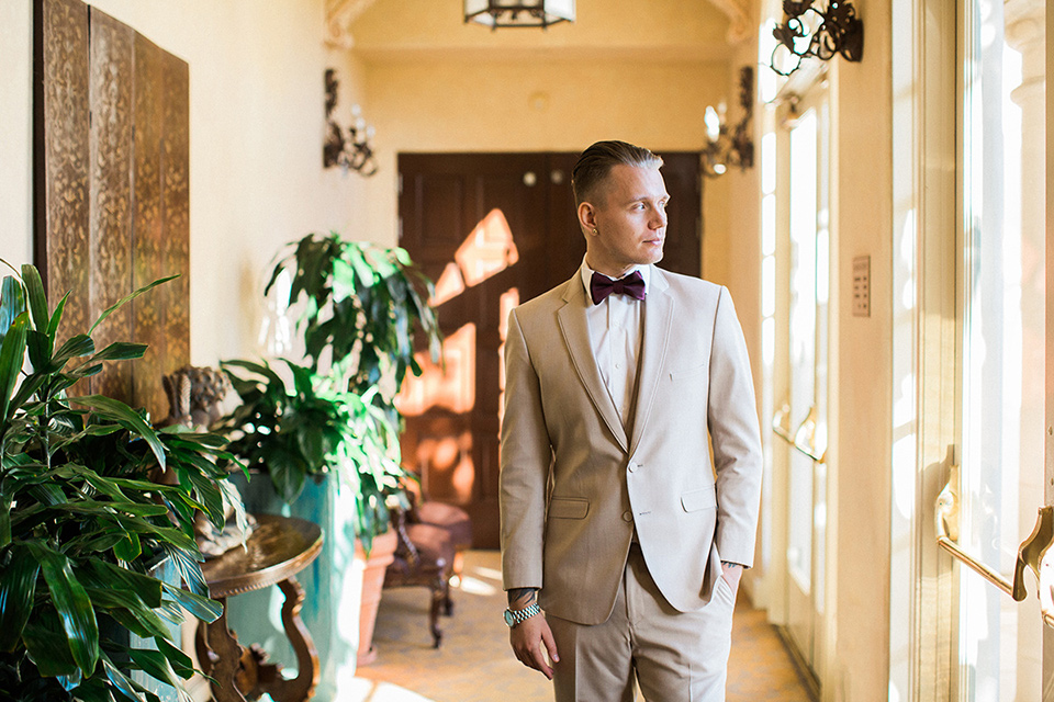 Huntington-bay-club-wedding-groom-walking-groom-in-a-tan-suit-with-a-burgundy-matte-bow-tie-and-brown-shoes