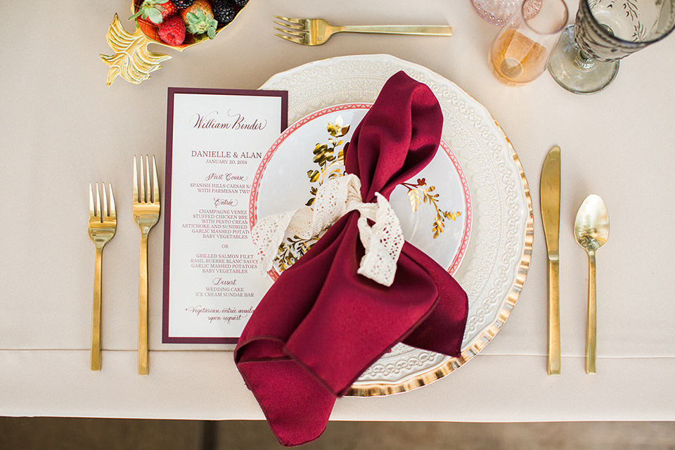Huntington-bay-club-wedding-silverware-white-plates-with-gold-silverware-and-red-napkins