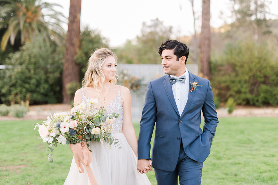 The-Lodge-at-Malibu-Lake-bride-and--groom-walking-towards--camera-bride-in-a-full-ball-gown-with-a-deep-v-crystal-detailed-bodice-groom-in-a-slate-blue-suit-with-a-grey-velvet-bow-tie