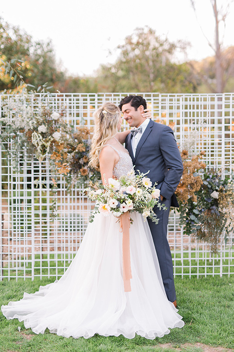 The-Lodge-at-Malibu-Lake-bride-and-groom-at-ceremony-space-bride-in-a-full-ball-gown-with-a-deep-v-crystal-detailed-bodice-groom-in-a-slate-blue-suit-with-a-grey-velvet-bow-tie
