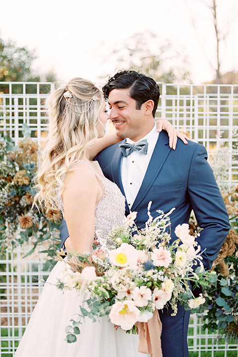 The-Lodge-at-Malibu-Lake-bride-and-groom-embrace-bride-in-a-full-ball-gown-with-a-deep-v-crystal-detailed-bodice-groom-in-a-slate-blue-suit-with-a-grey-velvet-bow-tie