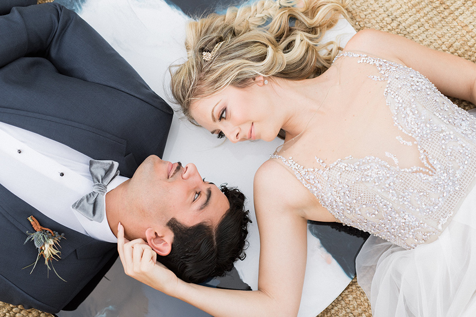 The-Lodge-at-Malibu-Lake-bride-and-groom-laying-down-bride-bride-in-a-full-ball-gown-with-a-deep-v-crystal-detailed-bodice-groom-in-a-slate-blue-suit-with-a-grey-velvet-bow-tie