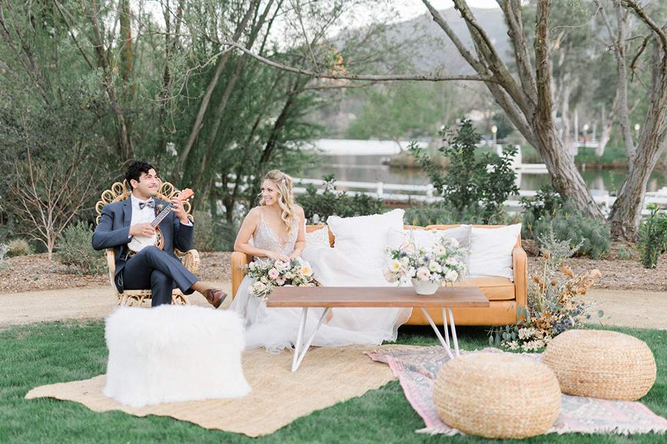 The-Lodge-at-Malibu-Lake-bride-and-groom-on-couches-bride-in-a-full-ball-gown-with-a-deep-v-crystal-detailed-bodice-groom-in-a-slate-blue-suit-with-a-grey-velvet-bow-tie