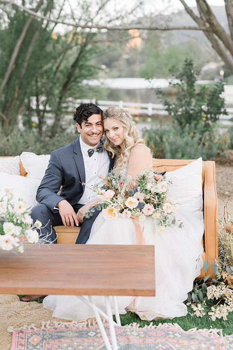 The-Lodge-at-Malibu-Lake-bride-and-groom-sitting-looking-at-the-camera-bride-in-a-full-ball-gown-with-a-deep-v-crystal-detailed-bodice-groom-in-a-slate-blue-suit-with-a-grey-velvet-bow-tie