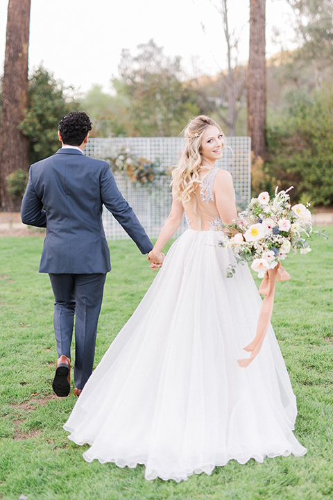 The-Lodge-at-Malibu-Lake-bride-and-groom-opeing-champs-bride-in-a-full-ball-gown-with-a-deep-v-crystal-detailed-bodice-groom-in-a-slate-blue-suit-with-a-grey-velvet-bow-tie