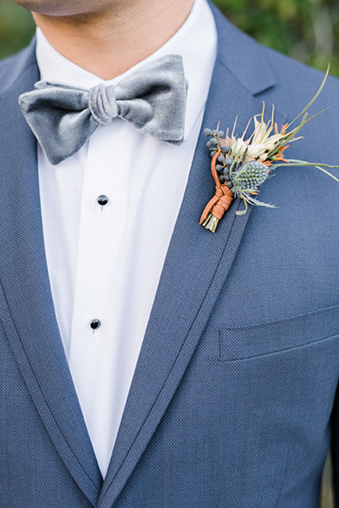 The-Lodge-at-Malibu-Lake-close-up-on-groomswear-groom-in-a-slate-blue-suit-with-a-grey-velvet-bow-tie