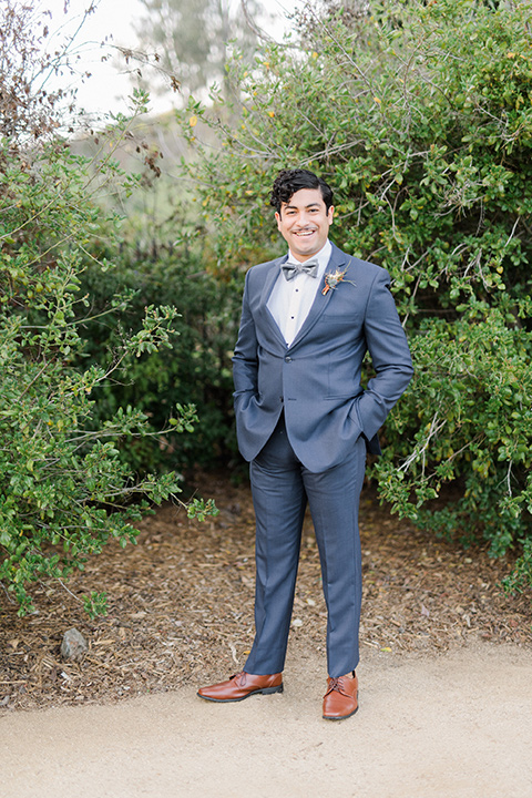 The-Lodge-at-Malibu-Lake-groom-standing-groom-in-a-slate-blue-suit-with-a-grey-velvet-bow-tie