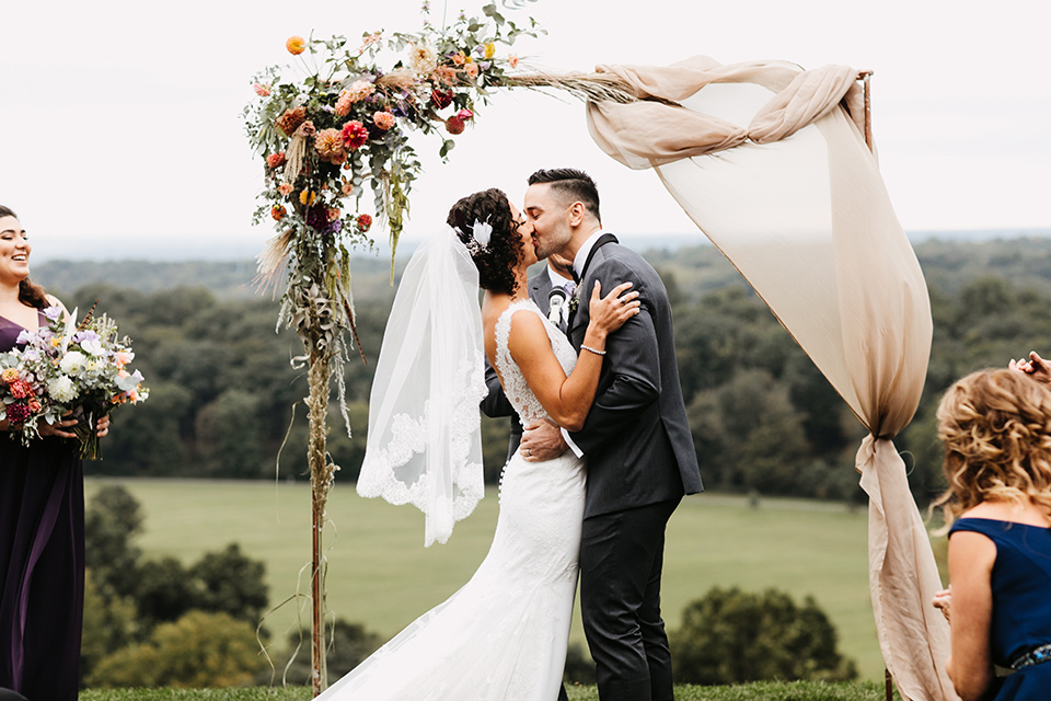 The-Mansion-at-Natirar-bride-and-grom-kiss-at-ceremony-bride-in-a-lace-fitted-dress-with-a-high-neckline-and-hair-up-groom-in-a-grey-tuxedo-with-black-trim-and-a-black-bowtie