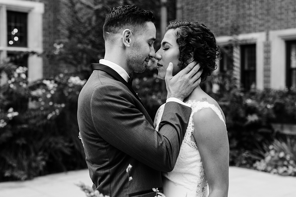 The-Mansion-at-Natirar-bride-and-groom-about-to-kiss-black-and-white-photo-bride-in-a-lace-fitted-dress-with-a-high-neckline-and-hair-up-groom-in-a-grey-tuxedo-with-black-trim-and-a-black-bowtie