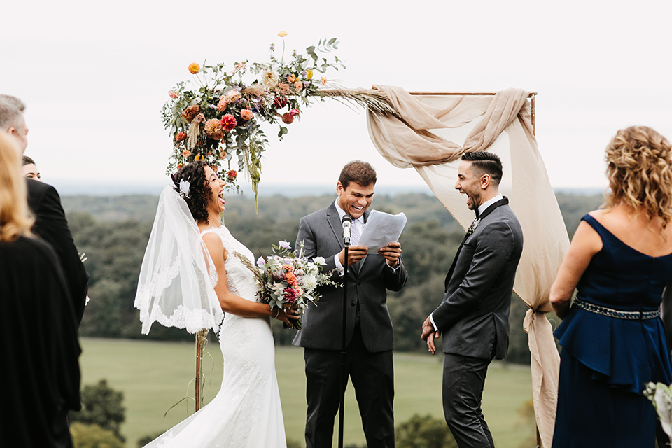 The-Mansion-at-Natirar-bride-and-groom-laughing-at-ceremony-bride-in-a-lace-fitted-dress-with-a-high-neckline-and-hair-up-groom-in-a-grey-tuxedo-with-black-trim-and-a-black-bowtie