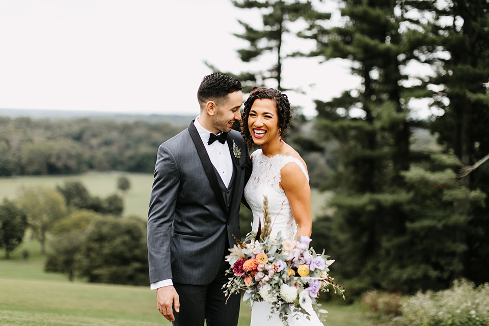 The-Mansion-at-Natirar-bride-and-groom-laughing-bride-in-a-lace-fitted-dress-with-a-high-neckline-and-hair-up-groom-in-a-grey-tuxedo-with-black-trim-and-a-black-bowtie