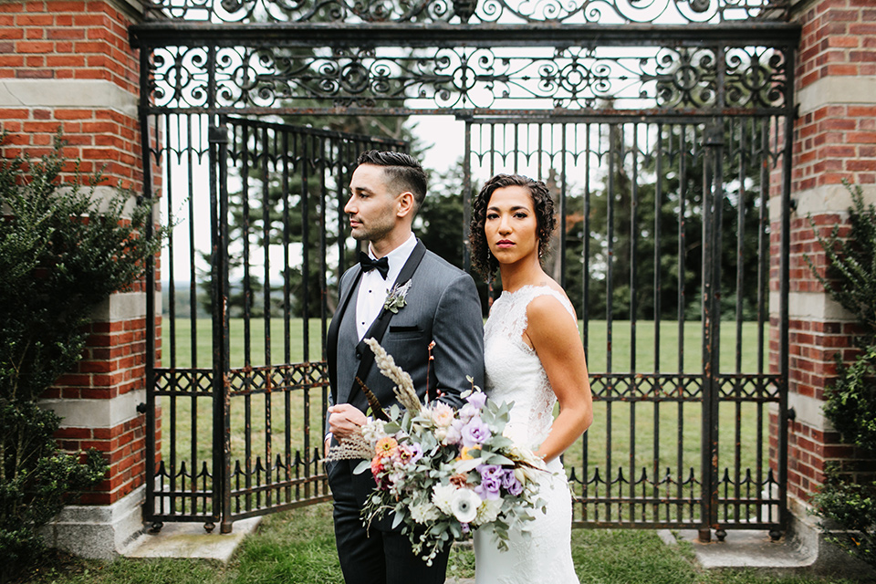The-Mansion-at-Natirar-bride-and-groom-looking-serious-by-iron-gate-bride-in-a-lace-fitted-dress-with-a-high-neckline-and-hair-up-groom-in-a-grey-tuxedo-with-black-trim-and-a-black-bowtie