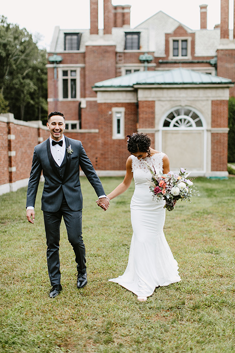 The-Mansion-at-Natirar-bride-and-groom-walking-dress-with-a-high-neckline-and-hair-up-groom-in-a-grey-tuxedo-with-black-trim-and-a-black-bowtie