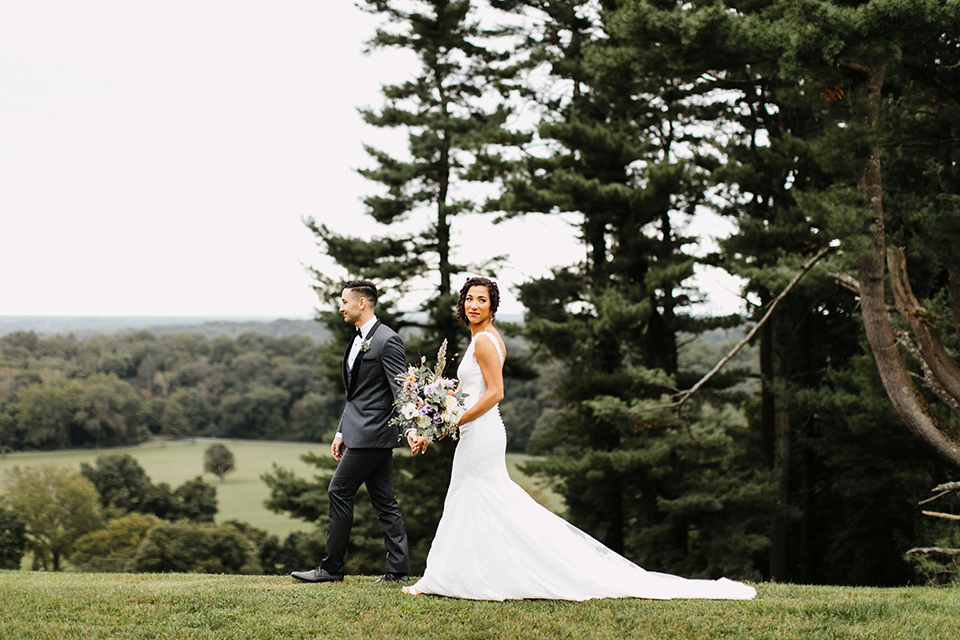 The-Mansion-at-Natirar-bride-and-groom-walking-by-the-forrest-bride-in-a-lace-fitted-dress-with-a-high-neckline-and-hair-up-groom-in-a-grey-tuxedo-with-black-trim-and-a-black-bowtie