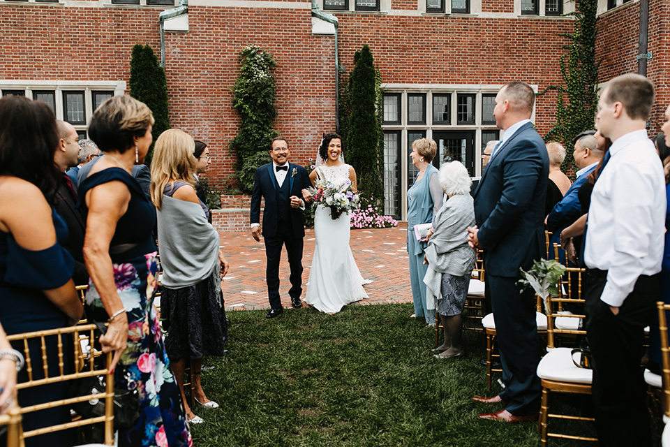 The-Mansion-at-Natirar-bride-coming-down-the-aisle-bride-in-a-lace-fitted-dress-with-a-high-neckline-and-hair-up-groom-in-a-grey-tuxedo-with-black-trim-and-a-black-bowtie