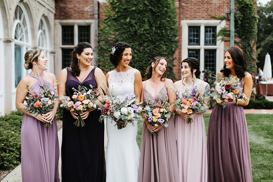 The-Mansion-at-Natirar-bridesmaids-bride-in-a-lace-fitted-dress-with-a-high-neckline-and-hair-up-bridesmaids-in-alternating-purple-dresses