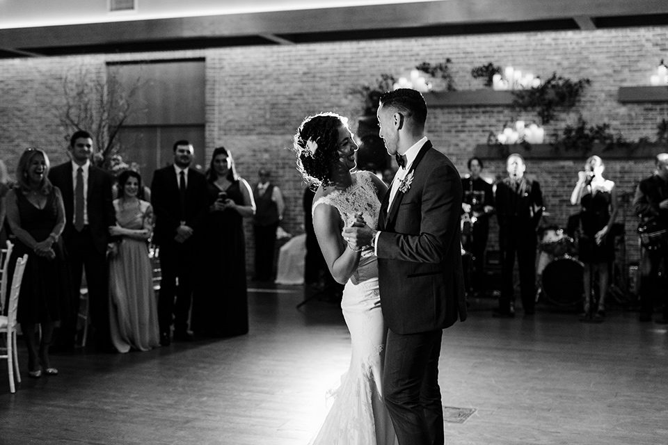 The-Mansion-at-Natirar-couple-first-dance-dress-with-a-high-neckline-and-hair-up-groom-in-a-grey-tuxedo-with-black-trim-and-a-black-bowtie