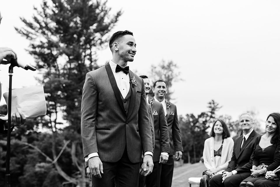 The-Mansion-at-Natirar-groom-looking-at-bride-coming-down-the-aisle-groom-in-a-grey-tuxedo-with-black-trim-and-a-black-bowtie