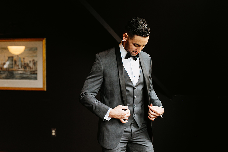 The-Mansion-at-Natirar-groom-putting-on-jacket-groom-in-a-grey-tuxedo-with-black-trim-and-a-black-bowtie