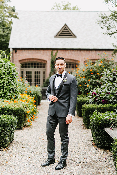 The-Mansion-at-Natirar-groom-standing-hands-in-pockets-groom-in-a-grey-tuxedo-with-black-trim-and-a-black-bowtie