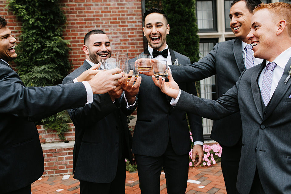 The-Mansion-at-Natirar-groomsmen-cheersing-groom-in-a-grey-tuxedo-with-black-trim-and-a-black-bowtie-groomsmen-in-grey-tuxedos-with-purple-ties