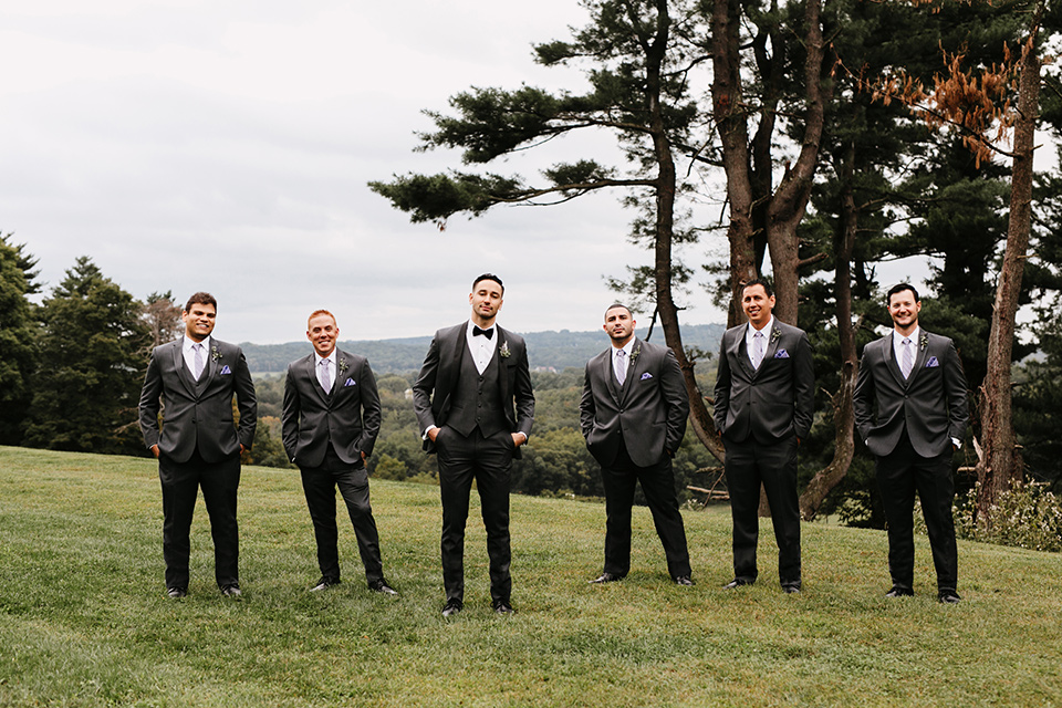 the-mansion-at-natirar-groomsmen-outside-groom-in-a-grey-tuxedo-with-black-trim-and-a-black-bowtie-groomsmen-in-grey-tuxedos-with-purple-ties
