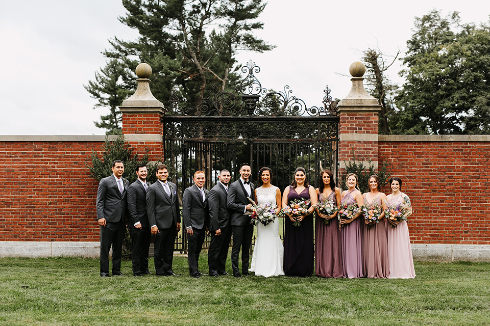 The-Mansion-at-Natirar-bridal-party-bridesmaids-in-different-shades-of-purple-dresses-groomsmen-in-grey-tuxeos-with-purple-ties-bride-in-a-lace-fitted-dress-with-a-high-neckline-and-hair-up-groom-in-a-grey-tuxedo-with-black-trim-and-a-black-bowtie