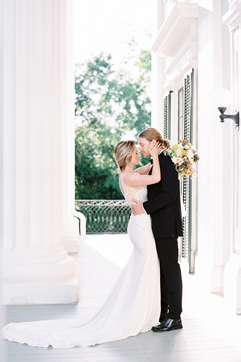 Taylor-Grady-House-shoot-bride-and-groom-facing-each-other-bride-touching-grooms-face-bride-in-a-fit-and-flar-silk-gown-with-an-open-back-detail-and-hair-in-a-loose-bun-groom-wearing-a-black-notch-lapel-tuxedo-with-a-black-bowtie-and-hair-in-a-bun
