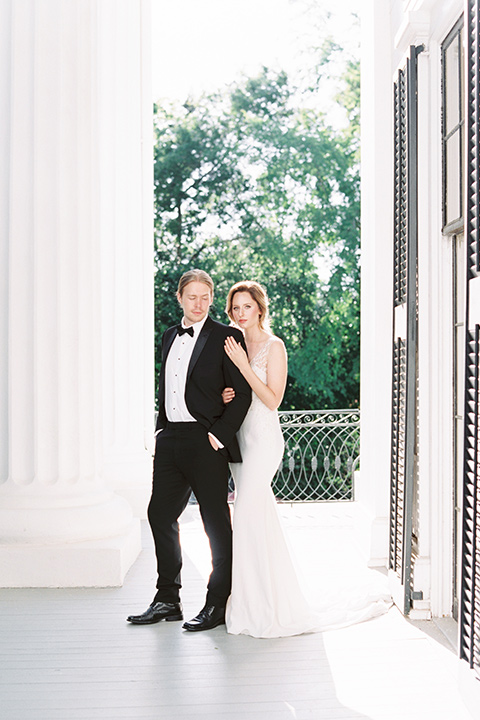 Taylor-Grady-House-shoot-bride-and-groom-standing-bride-behind-groom-grooms-hands-in-his-pockets-bride-in-a-fit-and-flar-silk-gown-with-an-open-back-detail-and-hair-in-a-loose-bun-groom-wearing-a-black-notch-lapel-tuxedo-with-a-black-bowtie-and-hair-in-a-bun