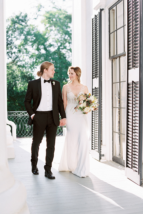 Taylor-Grady-House-shoot-bride-and-groom-walking-looking-at-each-other-bride-in-a-fit-and-flar-silk-gown-with-an-open-back-detail-and-hair-in-a-loose-bun-groom-wearing-a-black-notch-lapel-tuxedo-with-a-black-bowtie-and-hair-in-a-bun