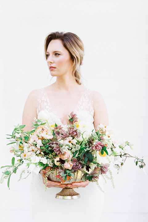 Taylor-Grady-House-shoot-bride-holding-flowers-bride-in-a-fit-and-flar-silk-gown-with-an-open-back-detail-and-hair-in-a-loose-bun-holding-a-big-bouquet-of-white-and-muted-toned-flowers