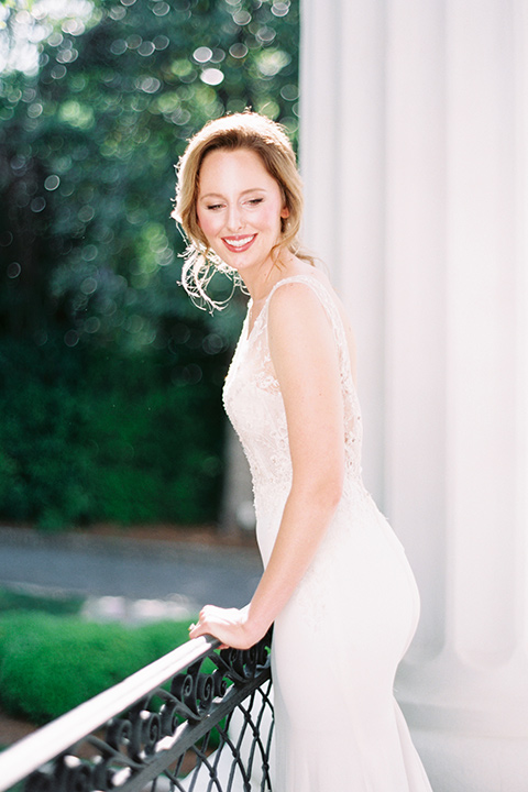 Taylor-Grady-House-shoot-bride-leaning-on-railing-bride-in-a-fit-and-flar-silk-gown-with-an-open-back-detail-and-hair-in-a-loose-bun