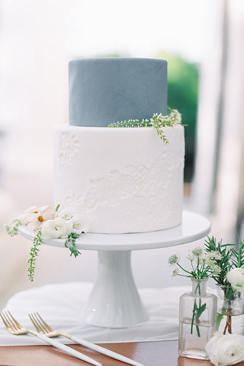 Taylor-Grady-House-shoot-cake-two-tier-cake-with-bottom-layer-is-a-clean-white-and-the-top-a-dusty-blue-shade-with-white-and-green-minimal-flowers-on-it