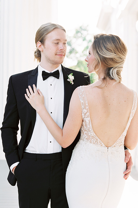 Taylor-Grady-House-shoot-close-up-on-bride-and-groom-groom-facing-camera-bride-back-towards-camera-bride-in-a-fit-and-flar-silk-gown-with-an-open-back-detail-and-hair-in-a-loose-bun-groom-wearing-a-black-notch-lapel-tuxedo-with-a-black-bowtie-and-hair-in-a-bun