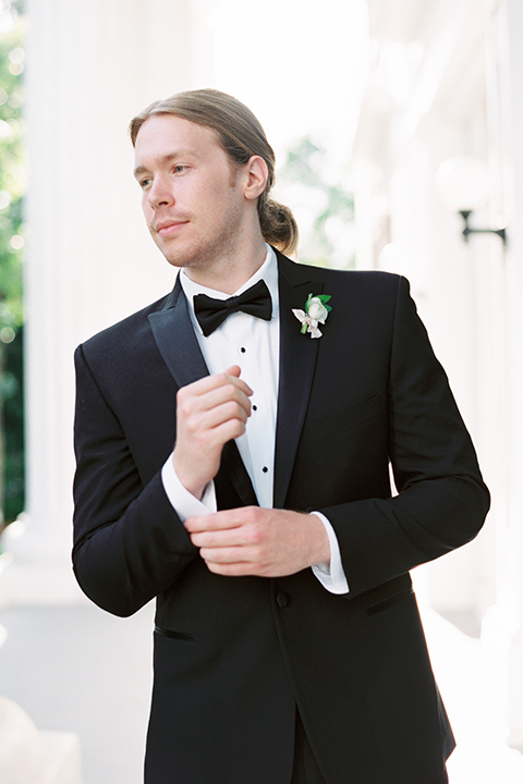 Taylor-Grady-House-shoot-close-up-on-groom-groom-wearing-a-black-notch-lapel-tuxedo-with-a-black-bowtie-and-hair-in-a-bun