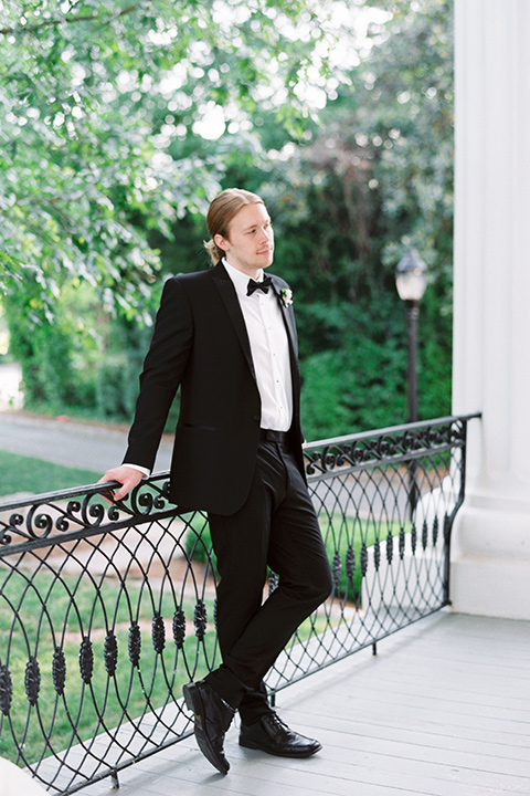 Taylor-Grady-House-shoot-groom-with-legs-crossed-groom-wearing-a-black-notch-lapel-tuxedo-with-a-black-bowtie-and-hair-in-a-bun