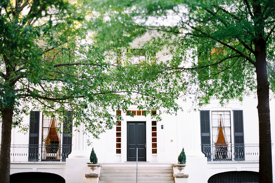 Taylor-Grady-House-shoot-outside-of-venue-green-lush-trees-in-the-foreground-the-white-house-in-the-background-with-white-bricks-and-black-trimming