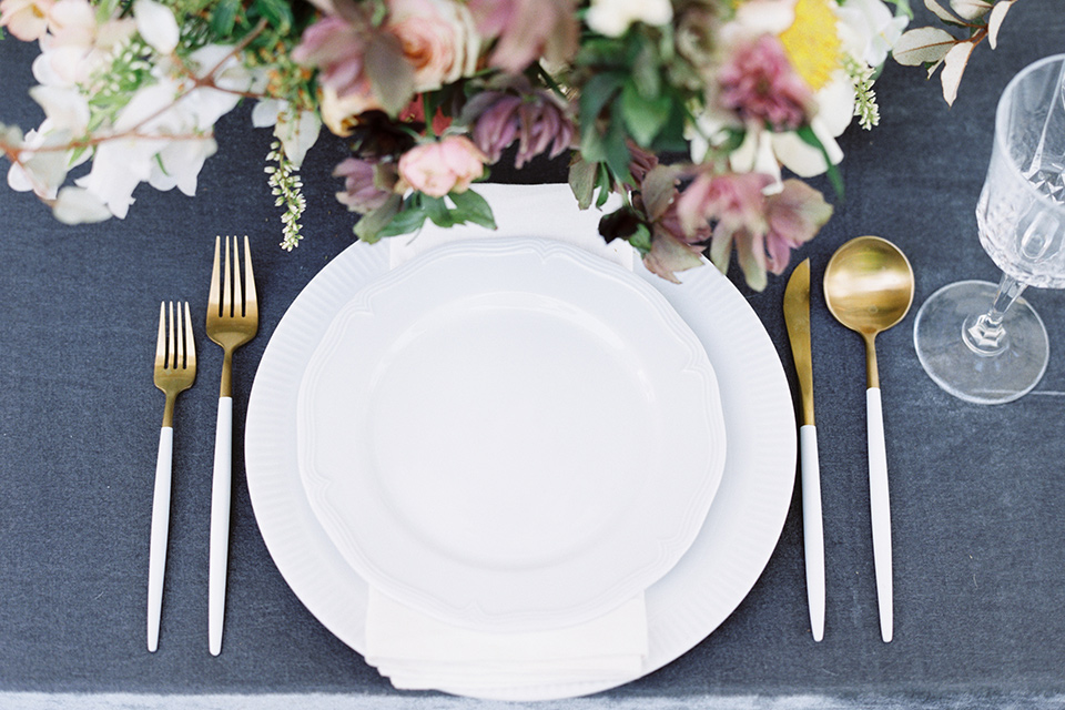 Taylor-Grady-House-shoot-tablewear-set-up-dusty-blue-velvet-linnen-with-simple-white-andmuted-gold-tablewear-with-muted-toned-florals-to-compliment-the-other-wedding-decor